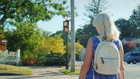 Ο τουρίστας γυναικών περνά το δρόμο στο σήμα φωτεινού σηματοδότη απόθεμα βίντεο