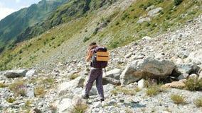 Ο τουρίστας γυναικών περπατά σε μια πετρώδη κοιλάδα σε ένα πεζοπορώ στα βουνά Κορίτσι με ένα σακίδιο πλάτης στην κάθοδο, μετακίνη στοκ φωτογραφία