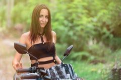 Ο τουρίστας γυναικών πρόκειται να πάει σε ένα μηχανικό δίκυκλο απόχρωση στοκ φωτογραφία με δικαίωμα ελεύθερης χρήσης