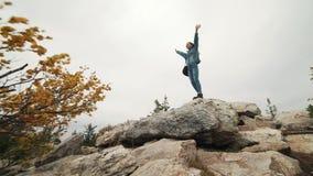 Ο τουρίστας γυναικών στην κορυφή είναι ευτυχής και επιτυχία εορτασμού Μια γυναίκα σε ένα σακάκι τζιν πάνω από τον κόσμο χαίρεται  φιλμ μικρού μήκους