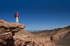 Ο τουρίστας εξετάζει μια κοιλάδα βουνών στοκ φωτογραφία με δικαίωμα ελεύθερης χρήσης