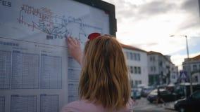 Ο τουρίστας εξετάζει το πρόγραμμα λεωφορείων στην οδό απόθεμα βίντεο