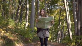 Ο τουρίστας εξετάζει το χάρτη στο ξύλο απόθεμα βίντεο