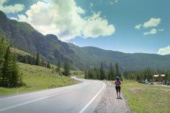 Ο τουρίστας κοριτσιών με ένα σακίδιο πλάτης πηγαίνει κατά μήκος του δρόμου στο βουνό Στοκ Φωτογραφίες