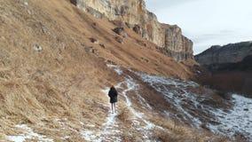 Ο τουρίστας κοριτσιών σε ένα κάτω σακάκι και ένα καπέλο περπατά κατά μήκος της πορείας τον πρώιμο χειμώνα σε ένα δύσκολο φαράγγι  φιλμ μικρού μήκους