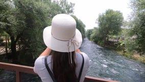 Ο τουρίστας κοριτσιών στο καπέλο στο κεφάλι του, που στέκεται σε μια ξύλινη γέφυρα και παίρνει μια όμορφη φύση ταμπλετών απόθεμα βίντεο