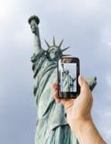 Ο τουρίστας κρατά ψηλά το τηλέφωνο καμερών στο άγαλμα της ελευθερίας στοκ εικόνες