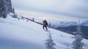 Ο τουρίστας με ένα σακίδιο πλάτης αναρριχείται στη χιονώδη κλίση απόθεμα βίντεο