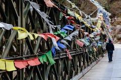 Ο τουρίστας με τη ζωηρόχρωμη θιβετιανή προσευχή δακρυ'ων σημαιοστολίζει τον κυματισμό και με τη γέφυρα πέρα από τον παγωμένο ποτα Στοκ εικόνα με δικαίωμα ελεύθερης χρήσης