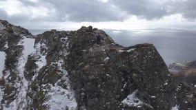 Ο τουρίστας φωτογράφων φύσης με τη κάμερα πυροβολεί στεμένος πάνω από το βουνό Όμορφη φύση Νορβηγία Lofoten απόθεμα βίντεο