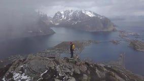 Ο τουρίστας φωτογράφων φύσης με τη κάμερα πυροβολεί στεμένος πάνω από το βουνό Όμορφη φύση Νορβηγία Lofoten φιλμ μικρού μήκους