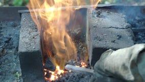 Ο του χωριού σιδηρουργός βάζει το κομμάτι προς κατεργασία σιδήρου στο κάψιμο των ανθράκων απόθεμα βίντεο