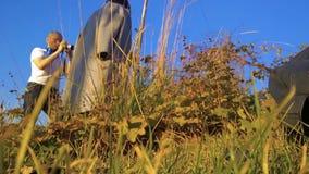 Ο το φωτογράφος αλλάζει τη κάμερα κατά βλάστηση ενός προτύπου στο πάρκο μεταξύ της ξηράς χλόης φιλμ μικρού μήκους
