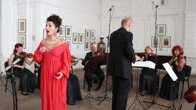 Ο τραγουδιστής γυναικών σε ένα κόκκινο φόρεμα και ένα ακριβό κόσμημα τραγουδά σε ένα δωμάτιο ενάντια στο σκηνικό μιας ομάδας και  φιλμ μικρού μήκους