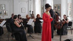Ο τραγουδιστής γυναικών στο κόκκινο κομψό φόρεμα βραδιού τραγουδά στους μουσικούς υποβάθρου με τα βιολιά και τον αγωγό στην αίθου απόθεμα βίντεο