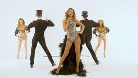 Ο τραγουδιστής σε ένα παλαιό φόρεμα με τα φτερά τραγουδά Μια ομάδα στους παλαιούς χορούς κοστουμιών Μια άσπρη ανασκόπηση το άτομο απόθεμα βίντεο