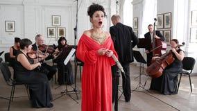 Ο τραγουδιστής στο κόσμημα και ένα κόκκινο φόρεμα τραγουδά σε ένα μικρόφωνο στο δωμάτιο ενάντια στο σκηνικό μιας ομάδας και ενός  φιλμ μικρού μήκους