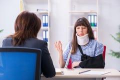 Ο τραυματισμένος επισκεπτόμενος δικηγόρος υπαλλήλων για τις συμβουλές για την ασφάλεια στοκ εικόνα