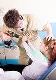 Ο τρελλός οδοντίατρος μεταχειρίζεται τα δόντια του ανεπιτυχούς ασθενή Ο ασθενής είναι τρομαγμένος Στοκ φωτογραφία με δικαίωμα ελεύθερης χρήσης
