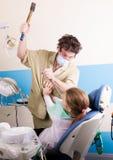 Ο τρελλός οδοντίατρος μεταχειρίζεται τα δόντια του ανεπιτυχούς ασθενή Ο ασθενής είναι τρομαγμένος Στοκ εικόνα με δικαίωμα ελεύθερης χρήσης