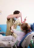 Ο τρελλός οδοντίατρος μεταχειρίζεται τα δόντια του ανεπιτυχούς ασθενή Ο ασθενής είναι τρομαγμένος Στοκ εικόνες με δικαίωμα ελεύθερης χρήσης
