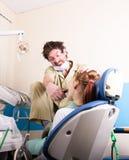 Ο τρελλός οδοντίατρος μεταχειρίζεται τα δόντια του ανεπιτυχούς ασθενή Ο ασθενής είναι τρομαγμένος Στοκ Εικόνες
