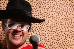 Ο τρελλός τραγουδιστής βράχου και κυλίνδρων με ένα μεγάλο μαύρο καπέλο, γυαλιά κομμάτων μπροστά από ένα τσιτάχ ξεφλουδίζει το υπόβ Στοκ φωτογραφία με δικαίωμα ελεύθερης χρήσης