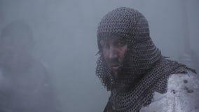 Ο τρομακτικός μεσαιωνικός στρατιώτης στο τεθωρακισμένο chainmail κοιτάζει γύρω στον καπνό απόθεμα βίντεο