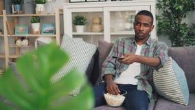 Ο τρυπημένος τύπος αφροαμερικάνων προσέχει την τρυπώντας ταινία στη TV που τρώει popcorn και που κρατά τον τηλεχειρισμό Το άτομο  φιλμ μικρού μήκους