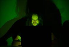 Ο τρυπημένος χρήστης εξετάζει τον υπολογιστή του κοιτάζοντας βιαστικά μέσω του Διαδικτύου Στοκ Φωτογραφίες
