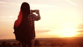 Ο τρόπος ζωής κοριτσιών σκιαγραφιών οδοιπόρων Hipster πυροβολεί το βίντεο του όμορφου ηλιοβασιλέματος φύσης στο τηλεφωνικό smartp φιλμ μικρού μήκους