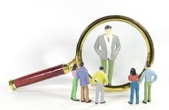 Ο τρύγος ενισχύει το γυαλί με το άτομο μεγάλης επιχείρησης και το μικρό πρότυπο παιχνίδι ανθρώπων Στοκ Φωτογραφίες