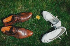 Ο τρύγος καλλωπίζει τα παπούτσια δέρματος με το άσπρο νυφικό υψηλό τακούνι στη βεραμάν χλόη Αγροτική φωτογραφία και αγροτική άποψ στοκ εικόνα