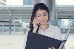Ο τρύγος τόνισε την εικόνα της ελκυστικής νέας ασιατικής ομιλίας γραμματέων στο τηλέφωνο και του κρατήματος του φακέλλου εγγράφων στοκ φωτογραφία