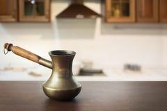 Ο τρύγος cezve με το μαύρο καφέ ξύλινο tabletop και η σύγχρονη κουζίνα ως υπόβαθρο για την επίδειξη ή το montage ο καφές σας π Στοκ Εικόνα