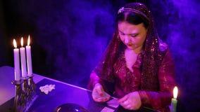 Ο τσιγγάνος σε ένα κόκκινο φόρεμα σε ένα μαγικό σαλόνι στον καπνό από το φως ιστιοφόρου διαβάζει το μέλλον στις κάρτες απόθεμα βίντεο