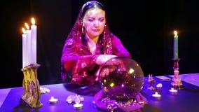 Ο τσιγγάνος σε ένα κόκκινο φόρεμα σε ένα μαντίλι διαβάζει το μέλλον σε μια σφαίρα καθρεφτών απόθεμα βίντεο