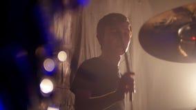 Ο τυμπανιστής και ο κιθαρίστας παίζουν τους ρόούς τους σε μια απόδοση ορχηστρών ροκ απόθεμα βίντεο