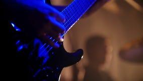 Ο τυμπανιστής και ο κιθαρίστας παίζουν τους ρόούς τους στην αργός-Mo σε μια απόδοση ορχηστρών ροκ απόθεμα βίντεο