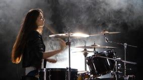 Ο τυμπανιστής σε ένα σακάκι δέρματος παίζει την ενεργητική μουσική Μαύρο υπόβαθρο καπνού Πλάγια όψη απόθεμα βίντεο