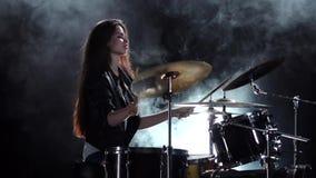 Ο τυμπανιστής σε ένα σακάκι δέρματος παίζει την ενεργητική μουσική Μαύρο υπόβαθρο καπνού Πλάγια όψη κίνηση αργή απόθεμα βίντεο
