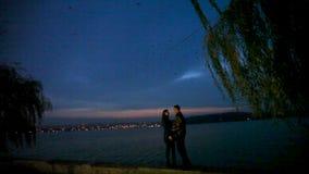 Ο τύπος αγκαλιάζει στοργικά και φιλά ένα κορίτσι ενάντια στο σκηνικό μιας πόλης νύχτας απόθεμα βίντεο