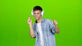 Ο τύπος ακούει την ενεργητική μουσική στα ακουστικά και χορεύει πράσινη οθόνη φιλμ μικρού μήκους