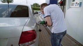 Ο τύπος βάζει το πυροβόλο όπλο στη δεξαμενή αερίου Ο νέος τύπος τρέχει το αυτοκίνητό του με τα καύσιμα απόθεμα βίντεο