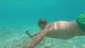 Ο τύπος βουτά κάτω από το νερό κρατώντας τη κάμερα στα χέρια του GoPro Hero7 απόθεμα βίντεο