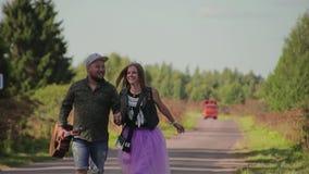 Ο τύπος δύο εραστών και ένα κορίτσι είναι σε μια εθνική οδό Η εκμετάλλευση του τύπου μια κιθάρα Έχουν τη διασκέδαση και επικοινων φιλμ μικρού μήκους