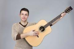 Ο τύπος είναι μουσικός με μια κιθάρα στο γκρίζο υπόβαθρο Στοκ Εικόνα