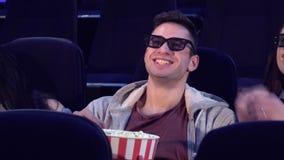 Ο τύπος κάθεται μεταξύ δύο κοριτσιών στη κινηματογραφική αίθουσα απόθεμα βίντεο
