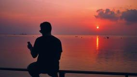 Ο τύπος κάθεται στην παραλία και εξετάζει το smartphone στο υπόβαθρο ηλιοβασιλέματος απόθεμα βίντεο