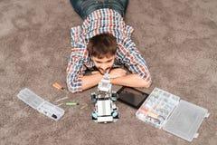 Ο τύπος κάθεται στο πάτωμα Δίπλα σε το είναι ένας ρινόκερος ρομπότ, μέρη των ρομπότ και εργαλεία Στοκ Εικόνες